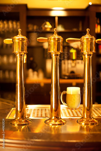 Luxury gold beer spigot at the brewery with a glass of beer