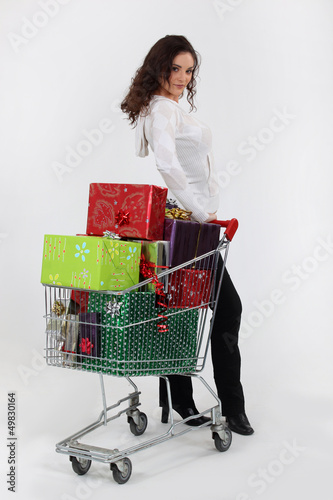 Woman with trolley full of Christmas presents