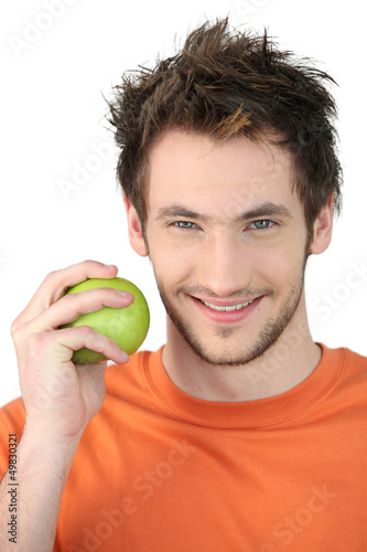 young man with orange shirt holding apple