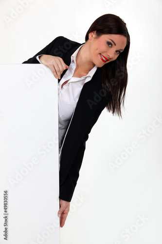 young businesswoman holding a blank advertising poster