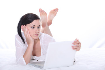 Woman laying on bed with laptop