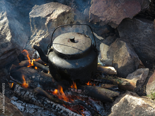 kettle tea on fireplace in wild nature