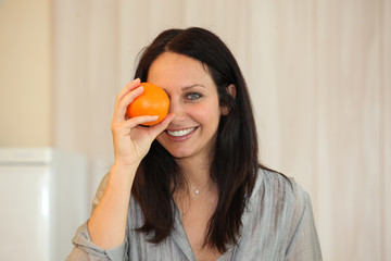 Woman holding an orange to her eye