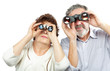 Elderly couple looks through binoculars