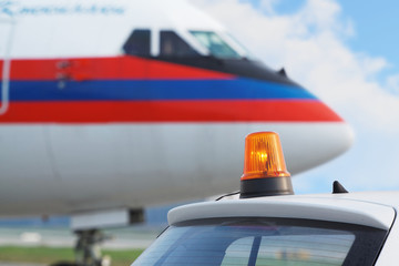 Car with flasher on roof and aircraft at airport