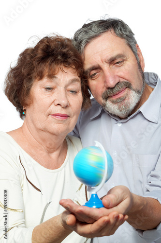 Elderly man and woman look at small globe