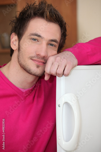 young man posing with arm on fridge door