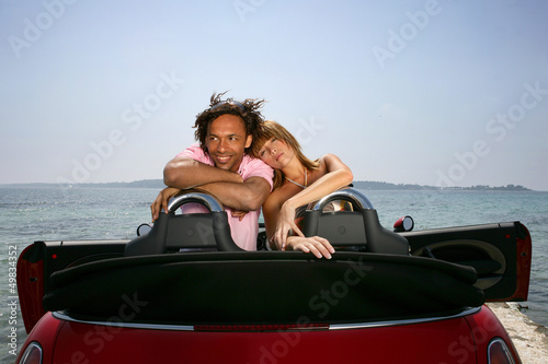 couple on a summer vacation embracing in their car