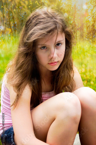 teenage girl looks serious outside in  sunlight