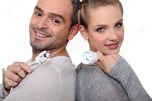 Couple with electrical plug stood back to back