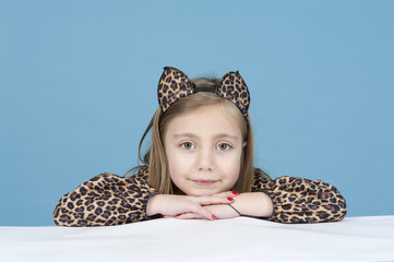 little girl disguised as a leopard, isolated on blue
