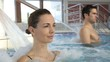 Woman enjoying hydrojet shower in spa pool