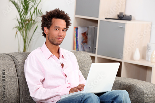 Couple sitting on sofa with computer