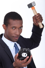 Man about to break open a piggy bank with a hammer
