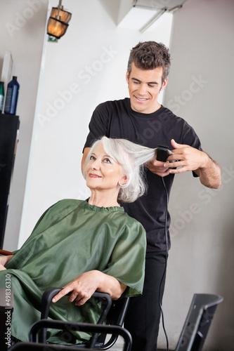 Hairstylist Straightening Female Client's Hair