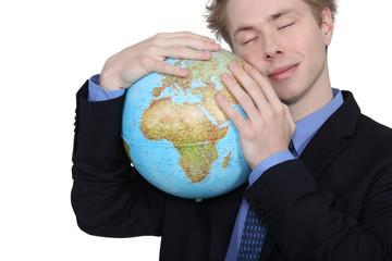 Businessman hugging a globe