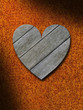 Weathered gray wood heart against rusty metal background