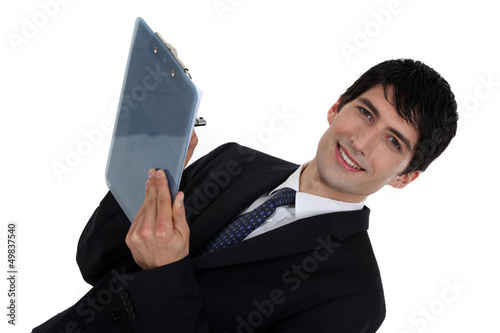 Businessman writing on clip-board