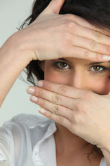 close shot of brunette with hands on face