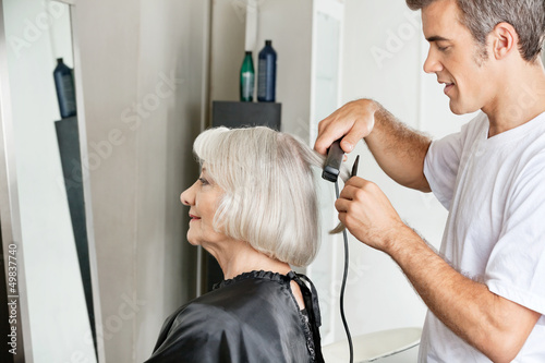 Hairstylist Straightening Customer's Hair