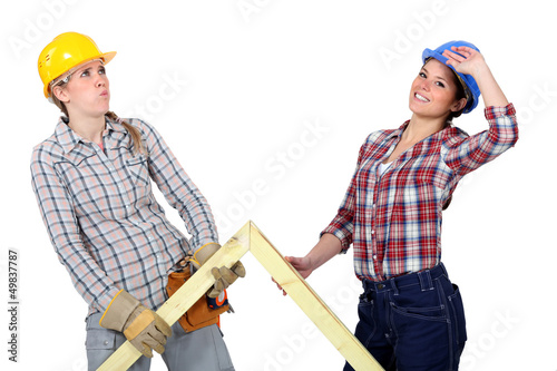 Women lifting wooden triangle