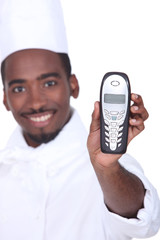 Smiling afro-American caterer with telephone, studio shot
