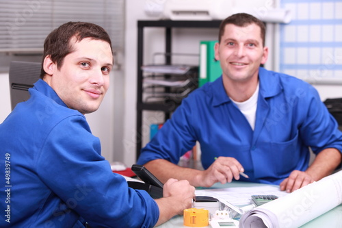 Two manual worker in the office checking stock levels