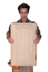 Carpenter holding wooden door