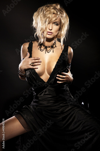 Sexy blonde beauty sitting in elegant black dress © pawelsierakowski