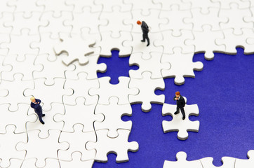 青色背景のジグソーパズルとビジネスマン