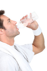 Man in gym clothes drinking a bottle of water