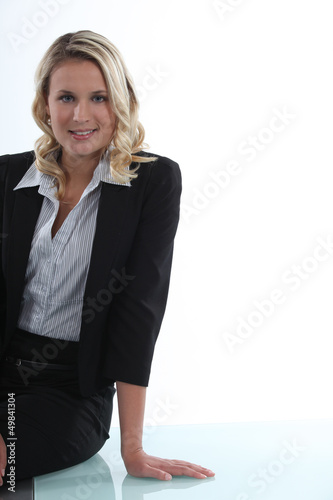 Attractive businesswoman leaning on a table
