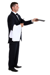 Profile view of male waiter holding out menu