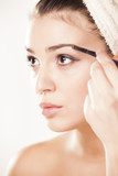 girl with towel on head draws her eyebrows with a Eye brow brush poster