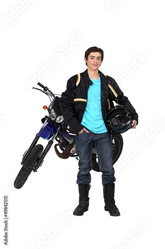 Teenager boy standing by a motorcycle