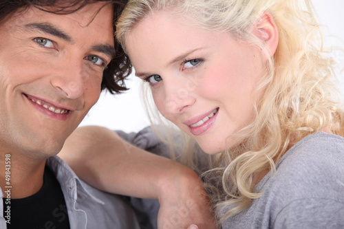 Couple stood close together on white background