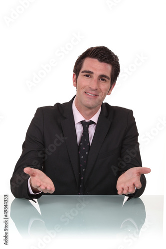 Friendly businessman sat at his desk