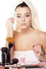 girl with towel on head fixes her makeup