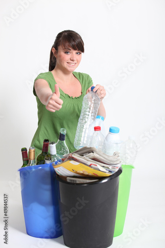 Brunette giving thumbs-up to recycling