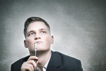 Junger Über-Manager nutzt seinen Denkstift.