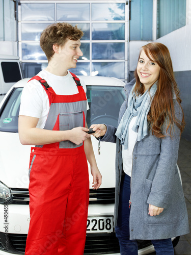 Car mechanic gives the car key to a female customer