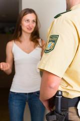 Polizist befragt Frau an Haustür zu Fall