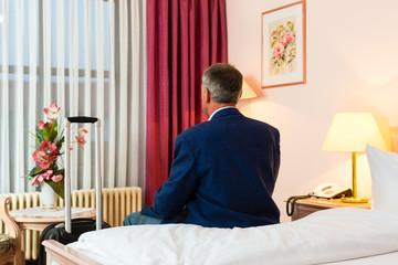 Älterer Mann sitzt auf dem Bett im Hotelzimmer