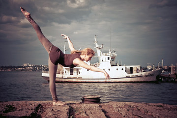 Sporty woman doing stretching exercise near the river