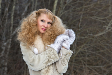 Smiling pretty young woman in a fur coat