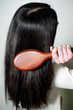 Woman combing her long hair with hairbrush