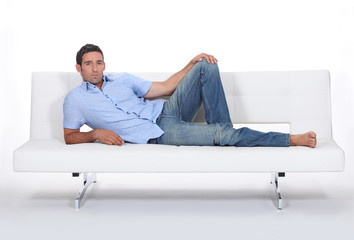 Sulky man lying on a couch