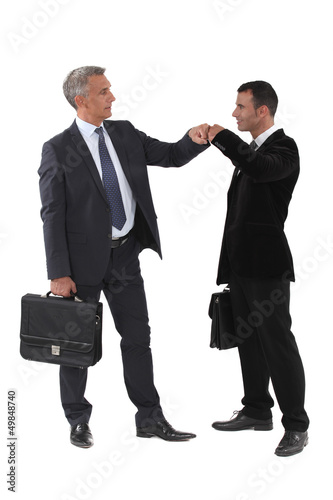 Two businessmen bumping fists
