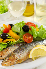 sardines with lemon and salad on the plate