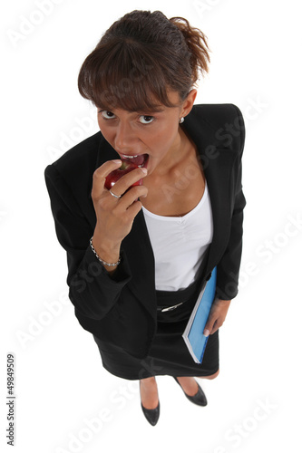 Businesswoman eating apple